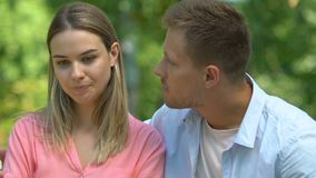 Unfaithful man hugging offended girlfriend, trying to reconcile after betrayal. Stock footage stock footage
