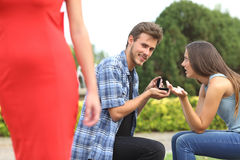 Unfaithful man looking another girl during proposal. Amazed unfaithful men looking another girl during marriage proposal and his girlfriend is angry Stock Photo