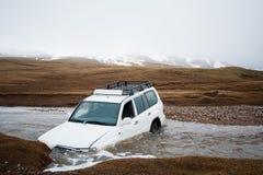 Unfall auf der Straße, Autounfall Jeep 4x4 fest im Gebirgsflussstrom Das Auto ertrunken im Fluss Extreme gefährliche Reise Lizenzfreies Stockfoto