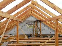 Unfertiges Dachbodenhaus, das Baubinder, Holzbalken, Dachgesimse, Bauholz überdacht Holzrahmenbau des Hausdachs lizenzfreies stockfoto