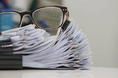 Unfertiges Dokument, Stapel Papierarchive mit Clipn auf Schreibtisch für Bericht und Gläser stockfotografie