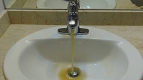 Unfiltered dirty water stream drain. Bathroom sink rusty water flow stock video footage