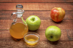 Unfiltered, raw apple cider vinegar. With mother - a cruet with a small glass  bowl surrounded by fresh  apples on rustic wood Stock Image