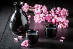 Unfiltered strong sake in black ceramics on table. Unfiltered strong sake in black ceramics on dark table royalty free stock photo