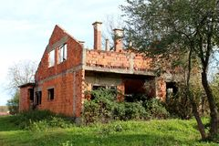 Unfinished abandoned brick house surrounded with high vegetation Royalty Free Stock Photo