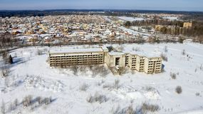 The unfinished and abandoned building. Stands on a snow-covered field Royalty Free Stock Photography