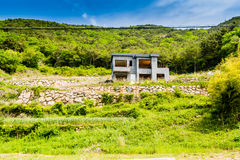 Unfinished abandoned gray concrete house in the side of a hill w Royalty Free Stock Images