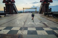 Unfinished abandoned metal bridge. Sporty girl runs from the start line stock image