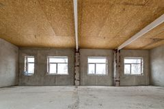Unfinished apartment or house big loft room under reconstruction. Plywood ceiling, plastered walls, window openings, cement floor. Construction and renovation stock images