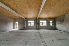 Unfinished apartment or house big loft room under reconstruction. Plywood ceiling, plastered walls, window openings, cement floor. Construction and renovation stock photo