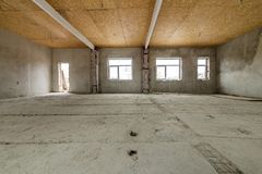 Unfinished apartment or house big loft room under reconstruction. Plywood ceiling, plastered walls, window openings, cement floor. Construction and renovation royalty free stock images