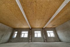 Unfinished apartment or house big loft room under reconstruction. Plywood ceiling, plastered walls, window openings, cement floor. Construction and renovation stock photography