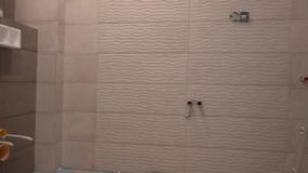 Unfinished bathroom room with tiles but without furniture. Construction industry. Handheld steadycam flycam movement panorama shot stock footage