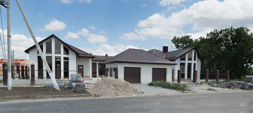 Unfinished beautiful cottage for two families with garages for car Royalty Free Stock Images