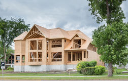 Unfinished brand new home being built. Horizontal image of an unfinished big brand new home being built surrounded by many green trees in the summer time Stock Photos