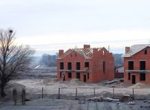An unfinished brick houses with a wooden roof frame is still under construction. A building site.  Stock Photography
