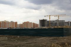 Unfinished building construction against already built houses behind green fence view from far. Building concept. Unfifished construction of new city view from royalty free stock photos