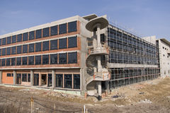 Unfinished Building on Construction Site. Unfinished concrete structure with curly stairs and installed windows royalty free stock photos