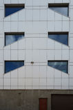 Unfinished building details of gray facade made of aluminum panels with doors and windows. Stock Photos