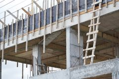 Unfinished building made of concrete slabs. Reinforcing bars and wooden planks Royalty Free Stock Image