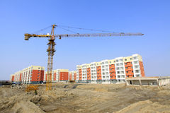 Unfinished building and tower crane, at a construction site Royalty Free Stock Images