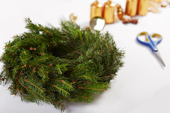Unfinished Christmas wreath. On a white table royalty free stock photo