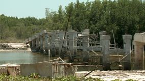 An unfinished concrete bridge over water. A concrete bridge sits, unfinished, over a small body of water stock video footage