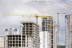 Unfinished concrete building and tower cranes against cloudy sky Stock Images