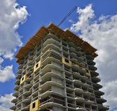 Unfinished Condo. Under construction high-rise residential building on a background of the cloudy sky Royalty Free Stock Images