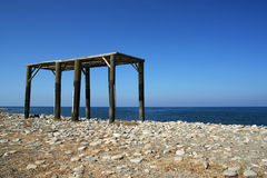 Unfinished Construction of a Summerhouse. Unfinished and abandoned construction of a summerhouse on the beach with the sea and cloudless sky in the background Stock Image