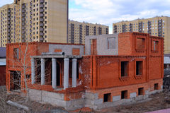 The unfinished cottage costs against high-rise buildings. Tyumen Stock Image