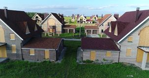 Unfinished cottages, abandoned cottages, a cottage town, several houses, Green lawn, View from above, aerial. Unfinished cottages, abandoned cottages, a cottage stock footage