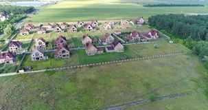 Unfinished cottages, abandoned cottages, a cottage town, several houses, Green lawn, View from above, aerial. Unfinished cottages, abandoned cottages, a cottage stock video footage