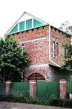 Unfinished country house of red brick with a green fence of metal royalty free stock images