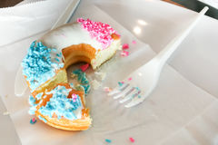 Unfinished donut glazed with sugar coating and sprinkles on plat Royalty Free Stock Photos