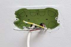 Unfinished electrical mains outlet socket with electrical wires. And TV cable - connector installed in plasterboard drywall for gypsum walls in apartment is royalty free stock photo