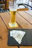 Unfinished glass of beer. Is on a table at the restaurant.  Money to pay is nearby Royalty Free Stock Images