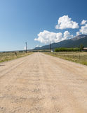 Unfinished graded dirt road to nowhere. Long straight dirt graded road across open countryside to distant mountains in Colorado stock photo
