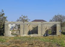 Unfinished house from a cinder block. The walls of the building under construction. Unfinished house from a cinder block. The walls of the building under Stock Photo