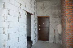 Unfinished house entrance room with metal entrance door. Close up royalty free stock photo