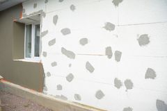 Unfinished house wall plastering with fiberglass mesh, plaster mesh and rigid foam insulation. Unfinished home wall plastering with fiberglass mesh, plaster mesh royalty free stock photography