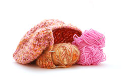 Unfinished knitted cap. With pink and brown clews and knitting needles on a white background Stock Images