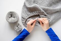 Unfinished knitting project in the hands of a young woman on a white background. A girl knits a wool cloth, near skeins royalty free stock photo
