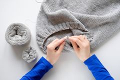 Unfinished knitting project in the hands of a young woman on a white background. The girl is knitting a woolen cloth royalty free stock images
