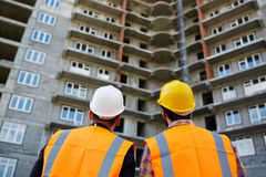 Unfinished real estate. Backs of men in uniform looking at new building Royalty Free Stock Photography