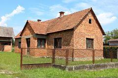 Unfinished red brick family house with worn down doors and faded window frames surrounded with rusted metal fence. Unfinished red brick family house with worn stock image