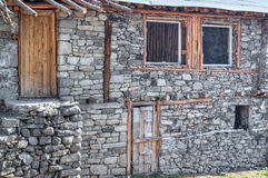 Unfinished stone house with wooden door and windows Stock Images