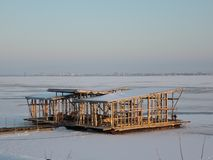 Unfinished structure on the frozen river on the background of winter city at sunset royalty free stock photo