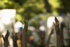 Unfocus-Bild mit Gruppe von Personen mit den Händen bis zum Himmel im Park lizenzfreie stockfotografie