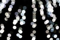 Unfocused abstraktes wei?es bokeh auf schwarzem Hintergrund defocused und verwischt vielen ringsum Licht stock abbildung